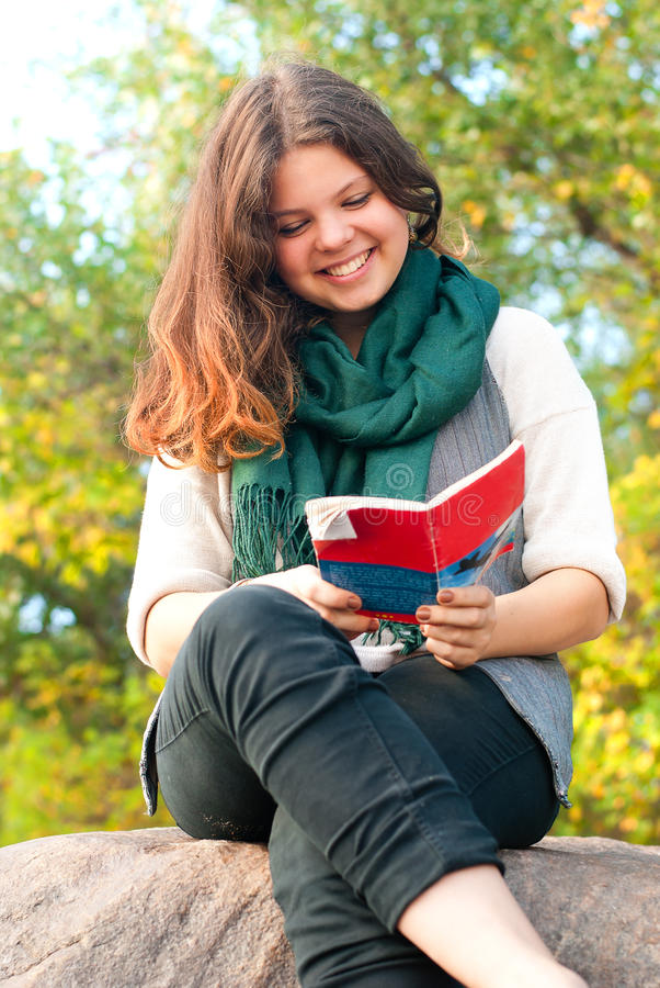 俏丽的女小学生在秋天公园读小册子 库存图片