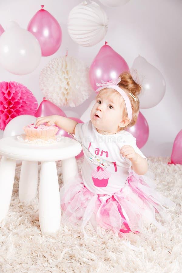 俏丽的女婴品尝生日蛋糕 库存照片