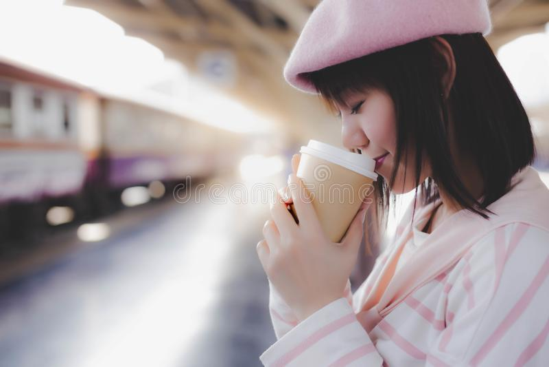 俏丽的妇女举行咖啡杯,饮料热的无奶咖啡在等待火车期间的早晨在火车站 库存照片
