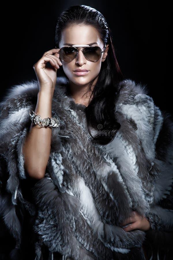 俏丽的妇女佩带的太阳镜和美丽的毛皮 图库摄影