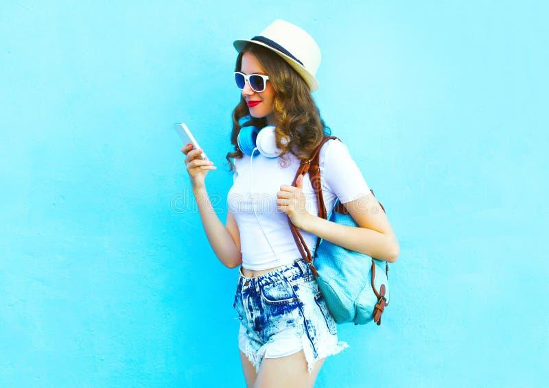 俏丽的妇女听到音乐和在五颜六色的蓝色的使用智能手机 免版税库存图片