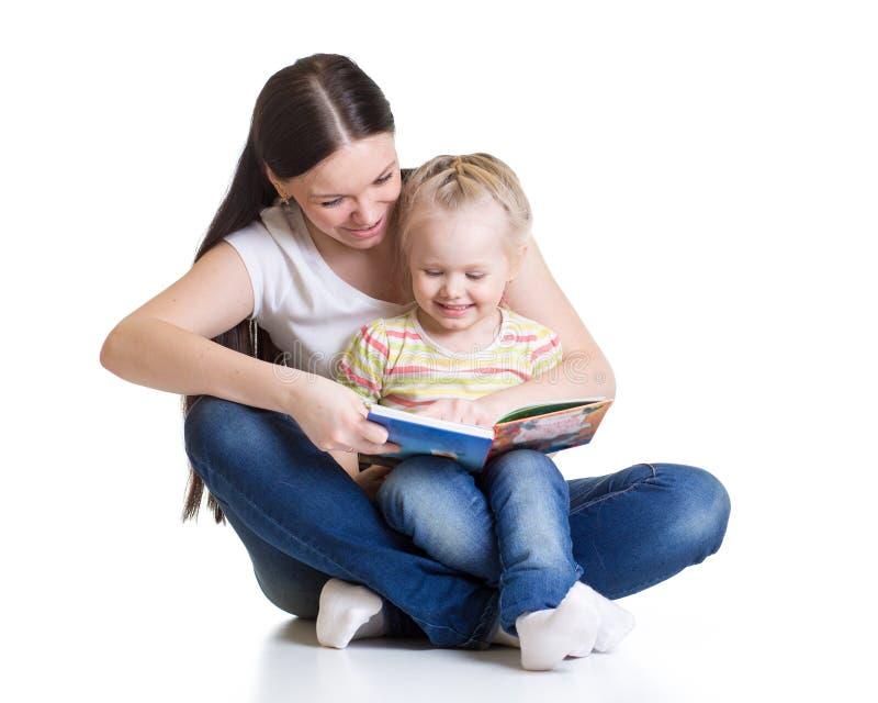 俏丽的妇女和她的儿童女儿读了在白色的一个故事 免版税库存图片
