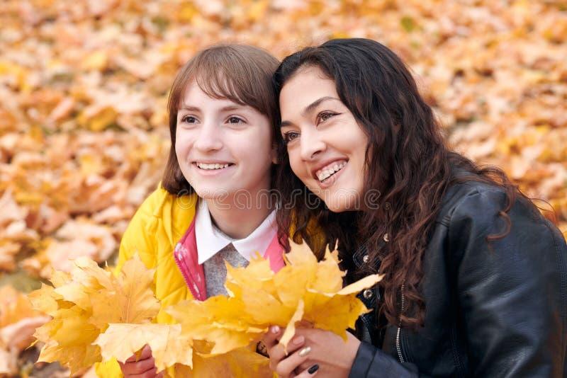 俏丽的妇女和青少年女孩摆在与束槭树的叶子在秋天公园 在秋季的美好的风景 库存照片
