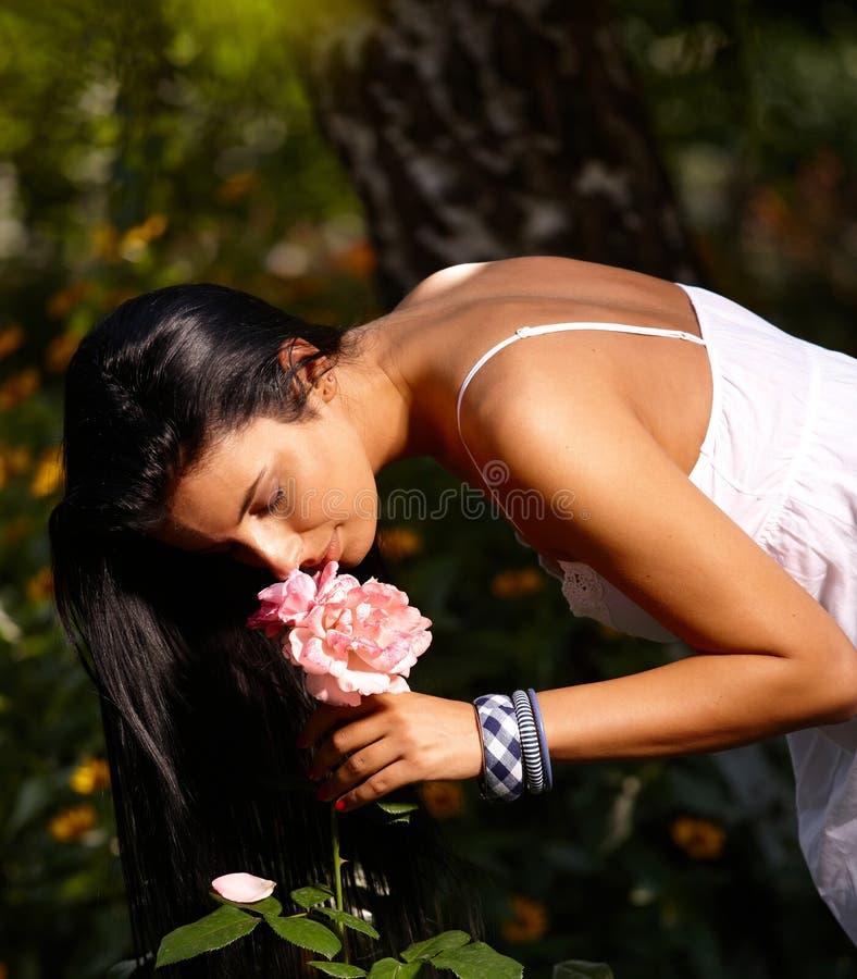 俏丽的妇女嗅到的花以绿色 库存图片