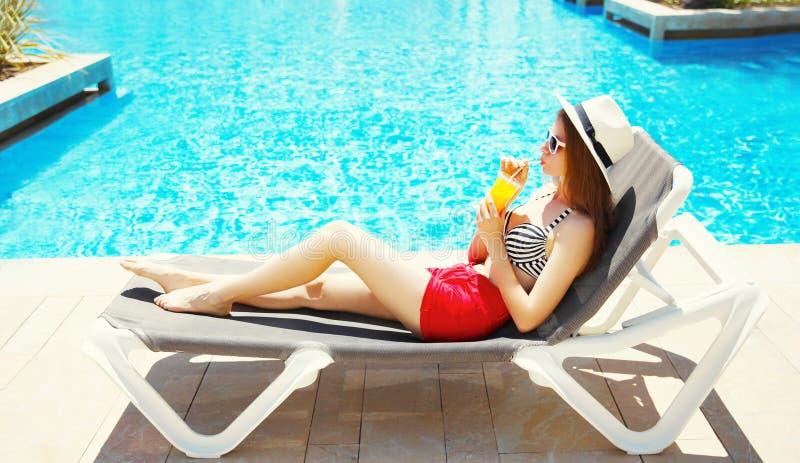 俏丽的妇女在一deckchair的夏天喝从杯子的汁液在一个大海水池 库存图片