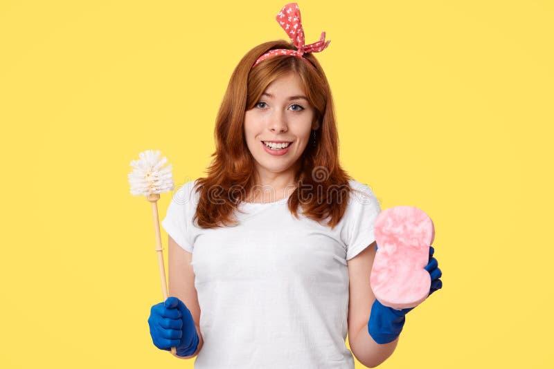 俏丽的妇女在佣人服务工作,做清扫的总体,举行刷子和海绵,穿白色T恤杉,并且橡胶手套,看 图库摄影