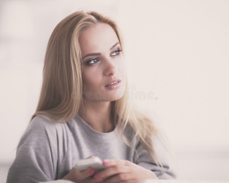 俏丽的妇女在她的说谎在长沙发的客厅传送信息 免版税库存照片