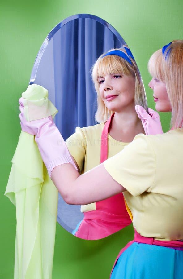 俏丽的妇女在家清洗镜子 库存图片