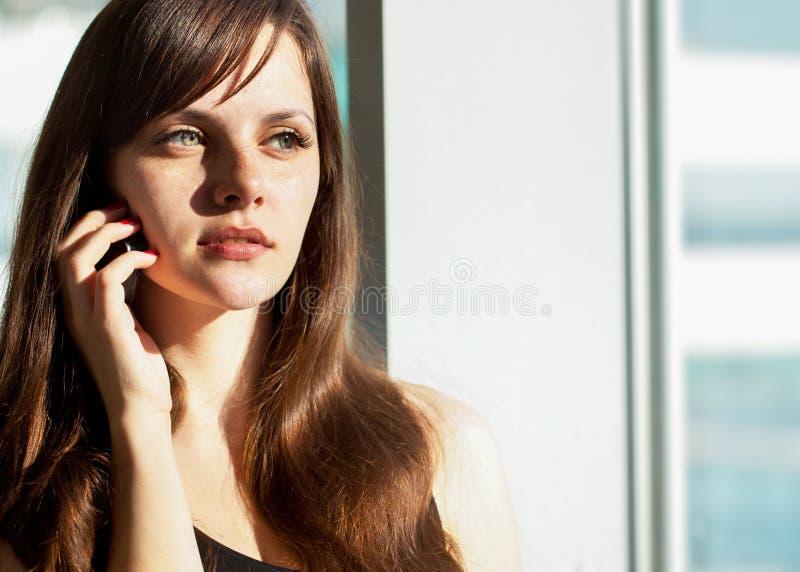 俏丽的妇女在家谈话在电话在窗口或她的办公室附近 免版税库存照片