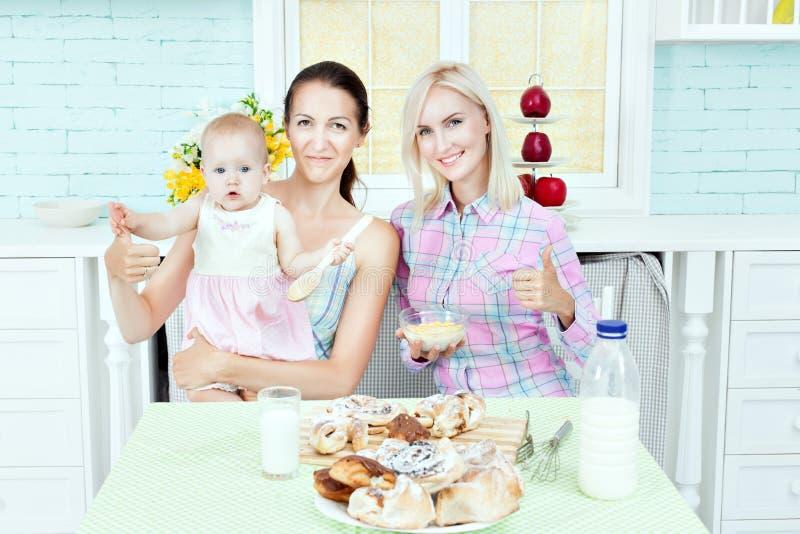 俏丽的妇女在有婴孩的厨房里 免版税图库摄影