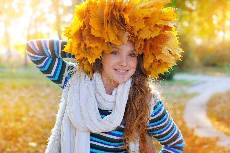 年轻俏丽的妇女在秋天公园做花圈叶子 免版税库存照片