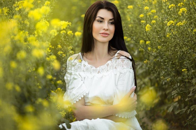 俏丽的妇女坐与野花花束在黄色领域在日落光,夏时的 免版税库存图片