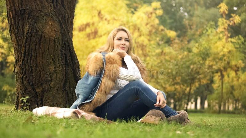 俏丽的妇女坐格子花呢披肩在树下在秋天公园,摆在为照相机 免版税图库摄影