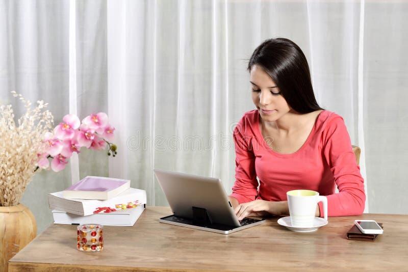 年轻俏丽的妇女工作在家庭办公室 库存照片