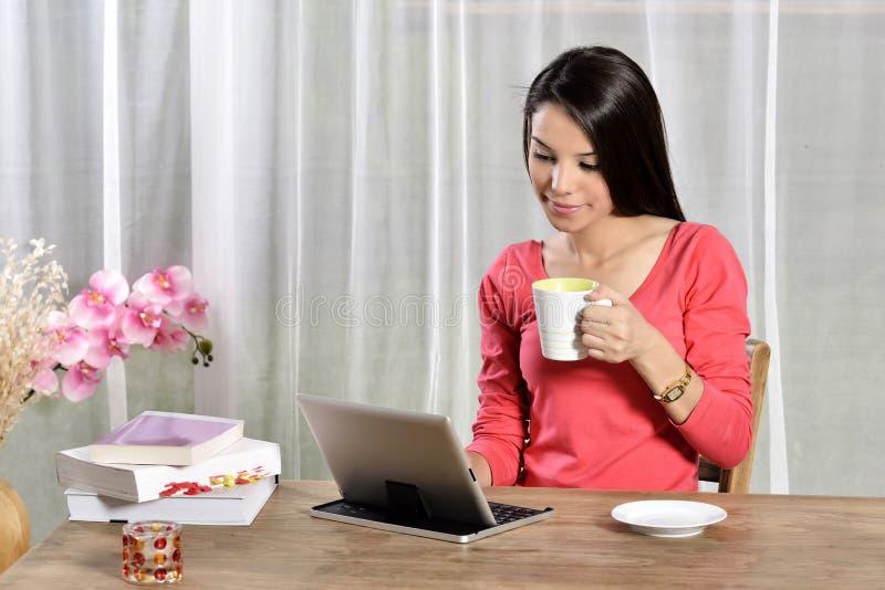 年轻俏丽的妇女工作在家庭办公室 免版税库存照片