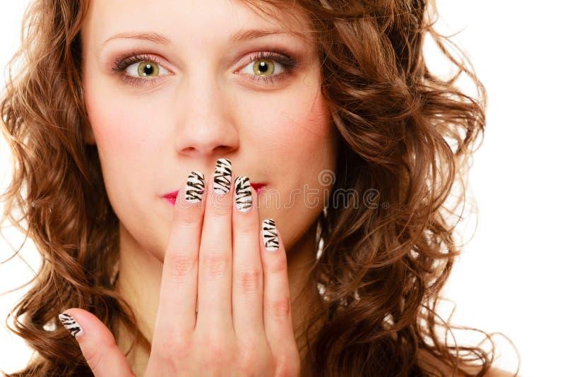 俏丽的妇女愉快的微笑用手包括她的嘴棕榈 免版税库存照片