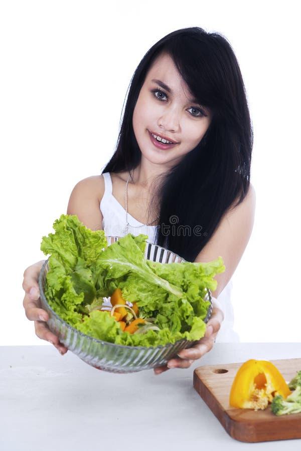 俏丽的妇女拿着菜沙拉 免版税库存图片