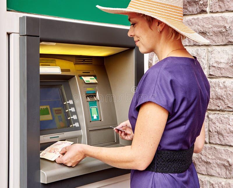 俏丽的妇女操作ATM 库存图片