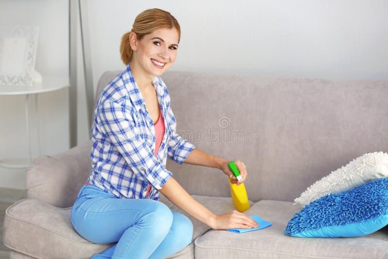 俏丽的妇女清洁沙发 免版税库存图片