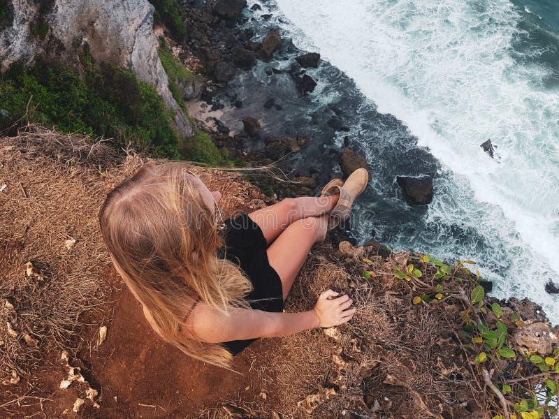 俏丽的妇女游人坐峭壁 免版税库存图片