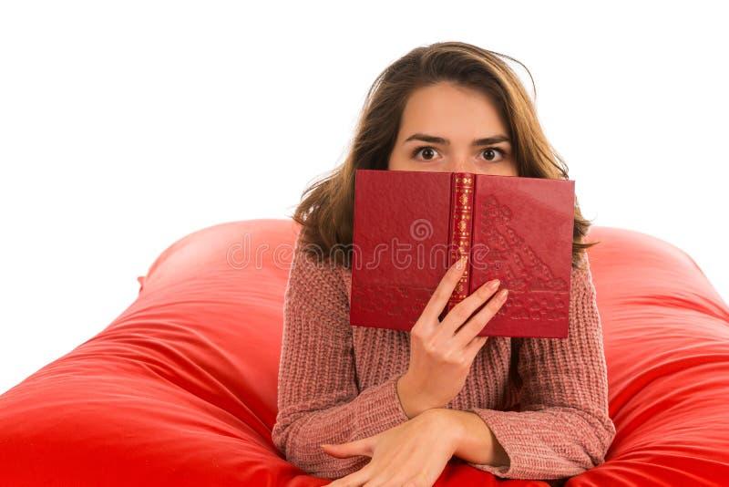 俏丽的妇女用书盖了面孔,当说谎在红色squar时 库存照片