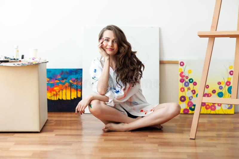 俏丽的妇女画家坐在帆布前面的地板和 库存图片