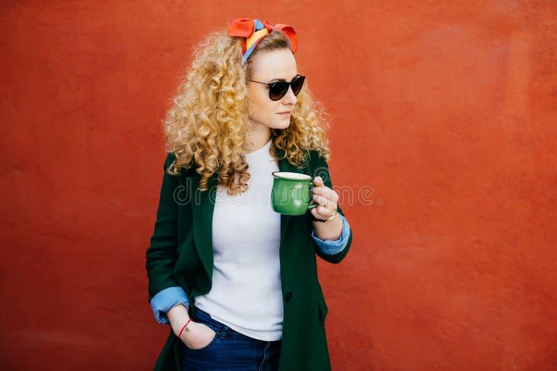 俏丽的妇女画象有卷发佩带的头饰带、时髦的拿着绿色茶在一韩的太阳镜和高尔夫球外套的 免版税库存照片