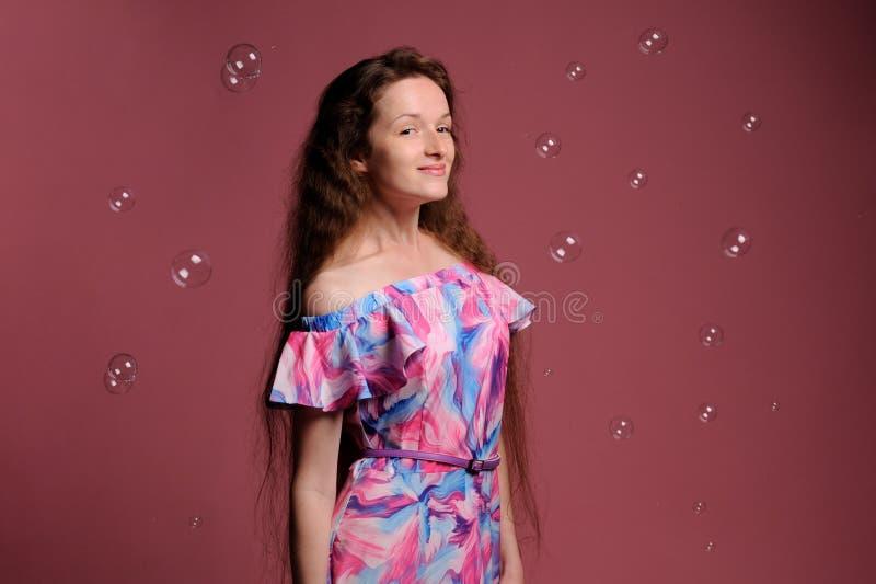 俏丽的妇女画象桃红色礼服的 库存图片