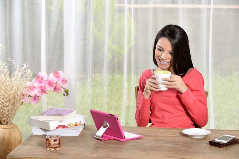 年轻俏丽的妇女看的Ipad  免版税库存图片