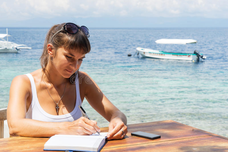 年轻俏丽的妇女自由职业者作家与笔记薄和电话一起使用在蓝色热带海前面 免版税库存照片
