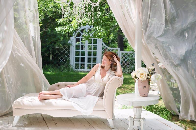 俏丽的妇女获得乐趣在夏天庭院眺望台 与花的丰富的室外生活范围庆祝的,茶会 免版税库存图片