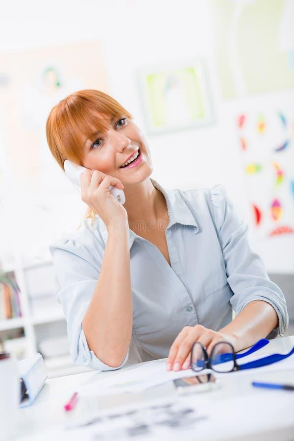 俏丽的妇女谈话在电话在办公室 免版税库存图片