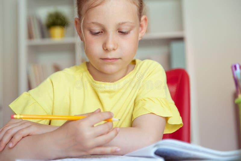 俏丽的学校女孩画象在教室学习在桌上 库存图片