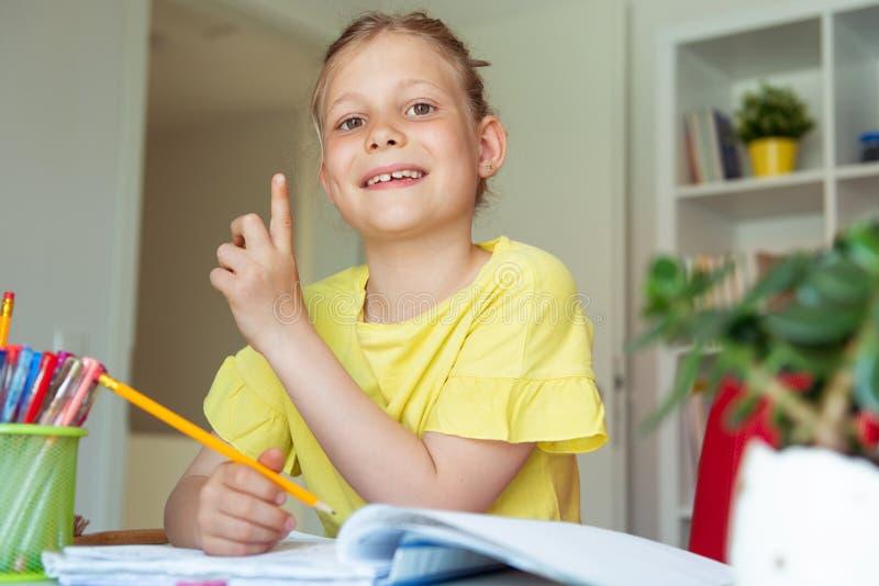 俏丽的学校女孩画象在教室学习在桌上 库存照片