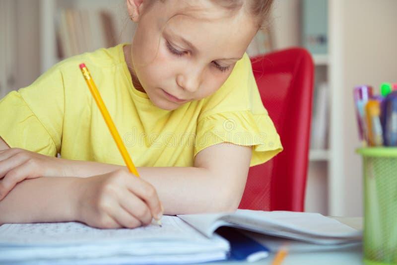 俏丽的学校女孩画象在教室学习在桌上 免版税库存照片