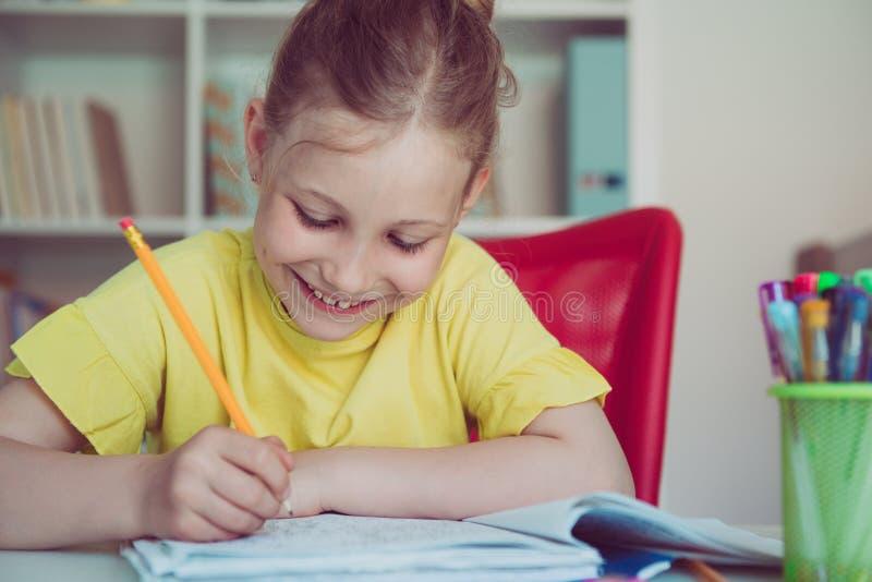 俏丽的学校女孩画象在教室学习在桌上 免版税库存图片