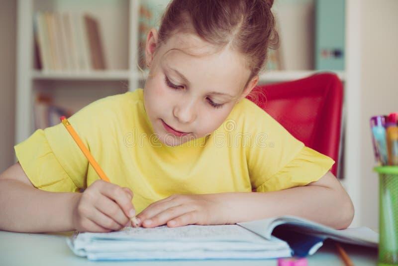 俏丽的学校女孩画象在教室学习在桌上 免版税图库摄影