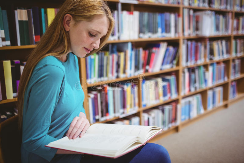 俏丽的学生坐椅子阅读书在图书馆里 库存图片