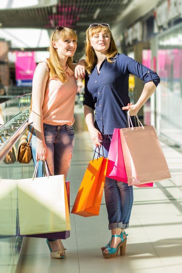 俏丽的孪生女孩获得与购物的乐趣在商城 免版税库存照片
