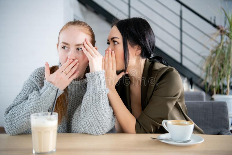 俏丽的对她的好奇朋友的妇女耳语的秘密 年轻女人告诉闲话对惊奇女性朋友 谣言概念 图库摄影