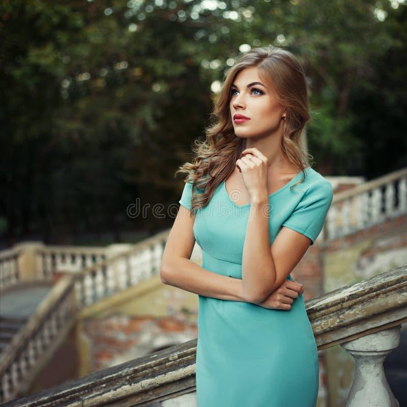 俏丽的少女室外生活方式画象,佩带在都市背景的蓝色礼服 创造性的颜色被定调子的图象 库存图片