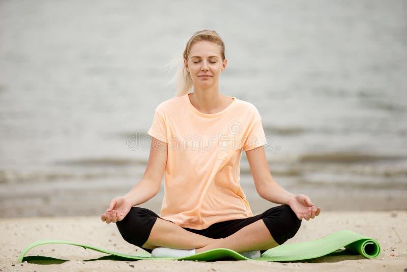 俏丽的少女放松的选址在瑜伽席子的莲花坐在沙滩在一温暖的天 免版税库存图片