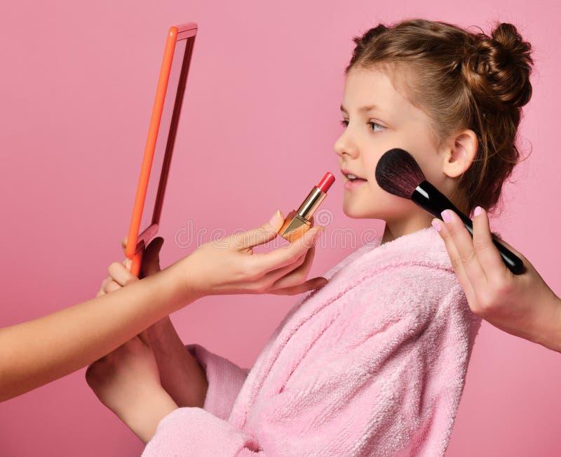 俏丽的少女青少年的女孩用在温泉沙龙的小圆面包在构成和头发期间评估她的在手镜的脸在桃红色 库存照片