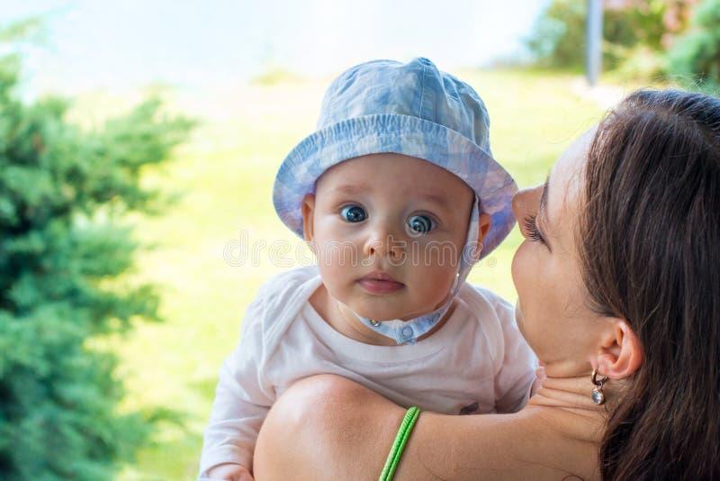 俏丽的帽子的,婴儿面孔画象母亲拥抱逗人喜爱的蓝眼睛的婴孩 库存图片