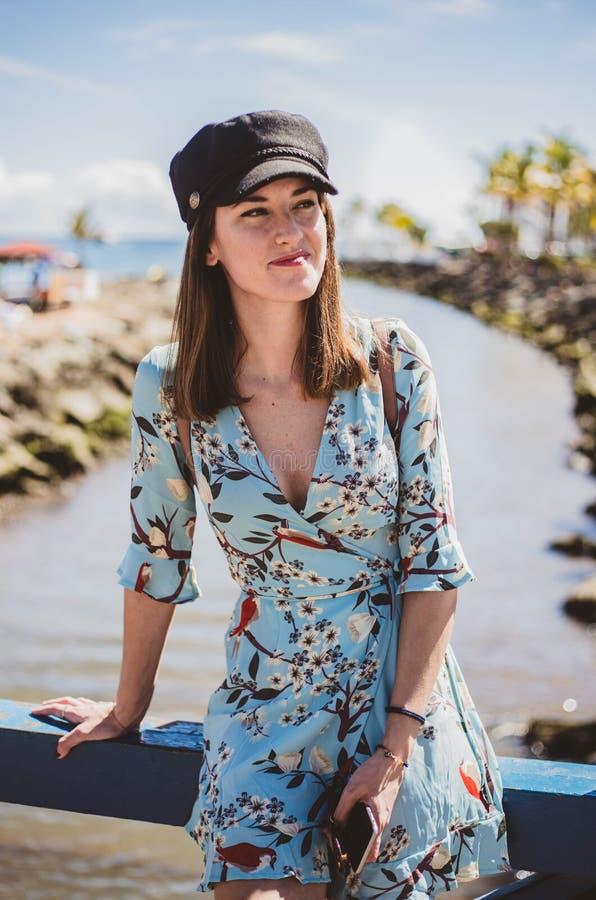 俏丽的年轻女人在看她的与一个黑盖帽的一个热带地方边 库存照片