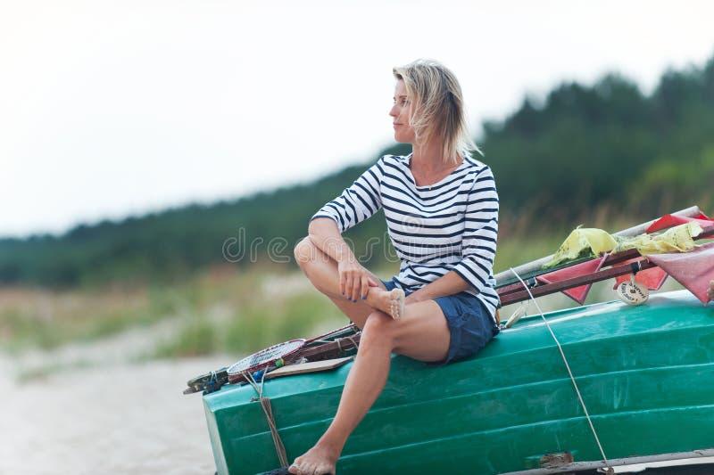 俏丽的年轻女人坐在海滩的木小船冥想沿海户外夏令时特写镜头水平色的 库存图片