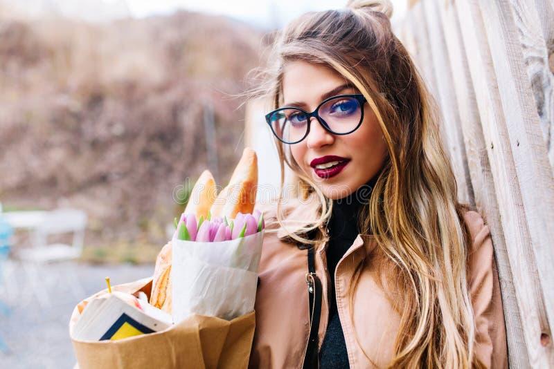 俏丽的年轻女人特写镜头画象有拿着从bakeshop的每天构成的纸袋 有长发的逗人喜爱的女孩 免版税图库摄影