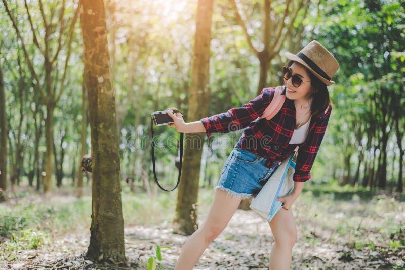 俏丽的年轻女人秀丽亚裔妇女微笑的生活方式画象获得乐趣在与数码相机的户外夏天 ?? 库存照片