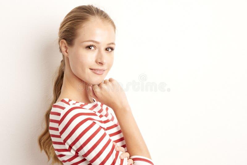 俏丽的年轻女人lookig演播室画象在照相机和微笑的,当站立对被隔绝的白色背景和使用与时 免版税库存图片