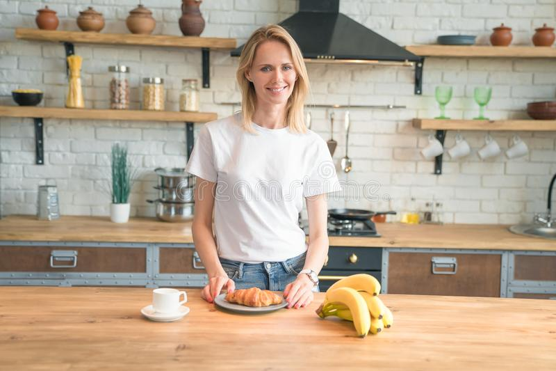 俏丽的年轻微笑的妇女在厨房里在家准备早餐 早晨咖啡,新月形面包,香蕉 r 图库摄影